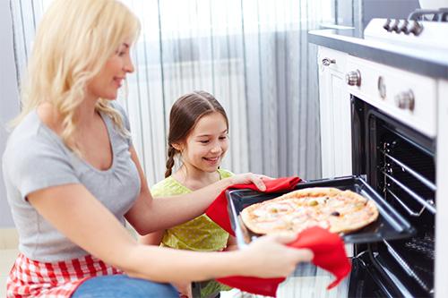 Mutter mit Kind gibt Pizza in den Ofen